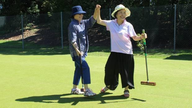 Sookhee Lee and JungA Kim celebrate their croquet success.