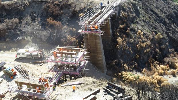 Repairs are made to the bridge at Truscotts Creek, one of several Midlands line bridges damaged by fire over Waitangi ...