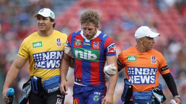 Brendan Elliot of the Knights leaves the ground after a head knock against South Sydney.