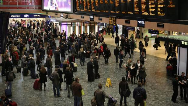 Passengers wait for trains at Euston station in London. The excavation site is next to the busy station.