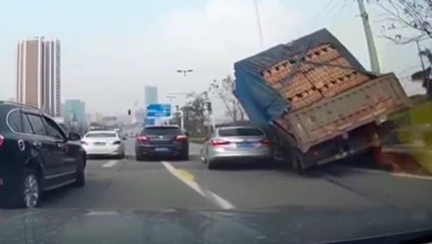Bricks on the slide off the back of a truck in China are about to crush the silver car.