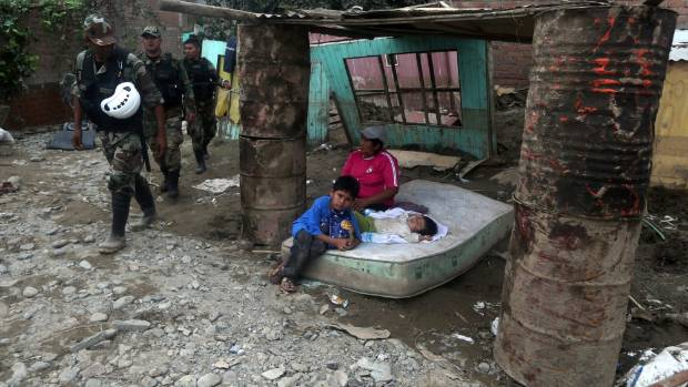 Flood survivors lie on a mattress near their home as rescue police officers walk past.