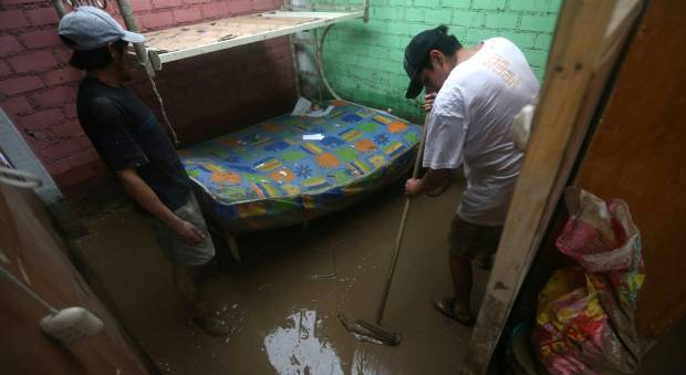 Flood survivors clean their house.