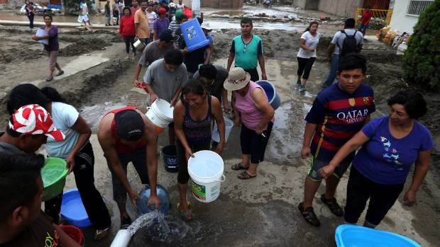 Flood survivors receive water after flooding and widespread destruction in Huachipa, Lima, Peru.