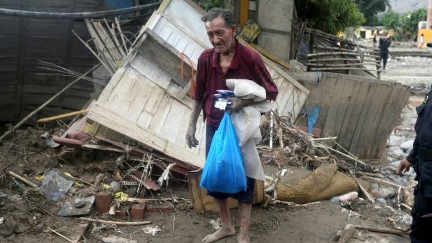 A flood survivor walks near debris in Huachipa, Lima, Peru.