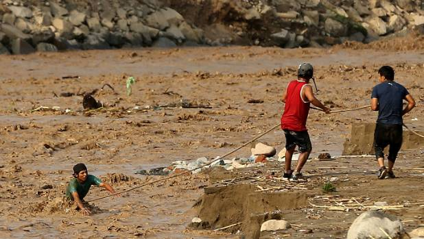 People try to cross the Rimac River in Peru, which among other river has already caused widespread flooding. Now, the ...