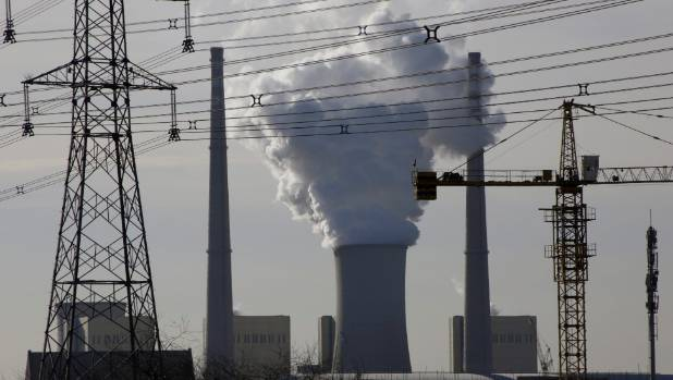 A coal-fired power plant is pictured near a construction site in Beijing. The city has closed its last remaining ...