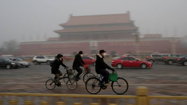 People wearing masks cycle past Tiananmen Gate during the smog after a red alert was issued for heavy air pollution in ...