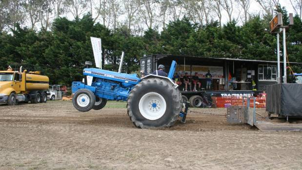 Modified tractors doing wheelies kept the crowds entertained during the  Tractor Pull competition at the Central ...