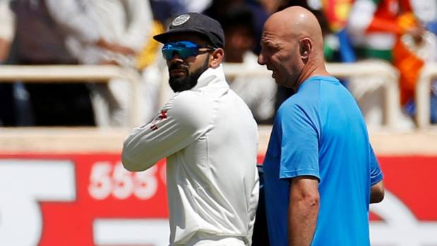 India captain Virat Kohli is attended to by team physio Patrick Farhart after suffering a shoulder injury on the first ...
