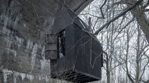 The Black Flying House is suspended by steel cables under an old railway arch in the middle of the woods in the Czech ...