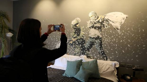 A visitor takes pictures for graffiti work painted by street artist Banksy showing an Israeli soldier and masked ...