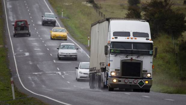 A truck heading south on State Highway 7 with a queue of cars behind it.