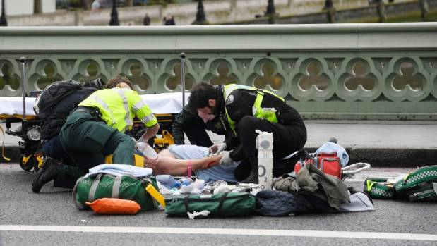 Paramedics treat an inured person after an incident on Westminster Bridge in London.