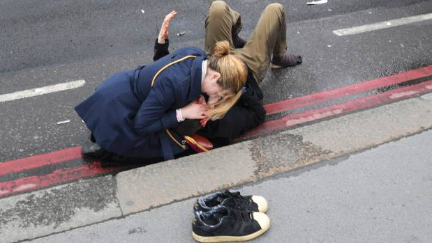 A woman assists an injured man after an incident on Westminster Bridge in London.