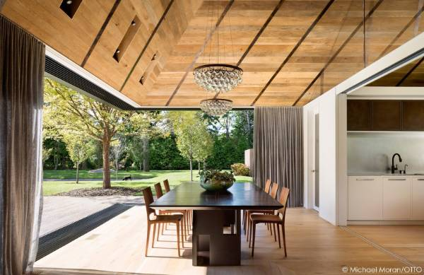 Sliding doors peel back from the corner of the house, opening it right up to the outdoors.
