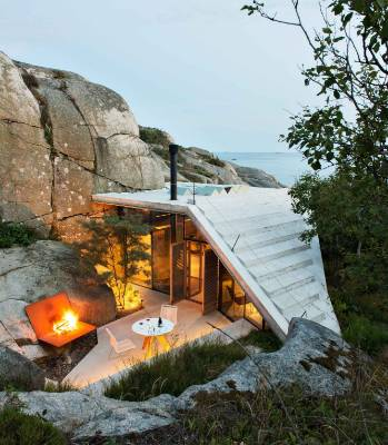 Although the cliff-side building occupies a small footprint, the space expands vertically over four levels, which ...