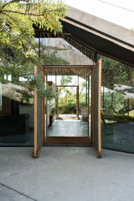 Accessible via a long boarded walkway, the house offers a sheltered atrium formed by the building and the cliffs.