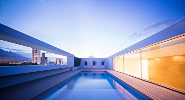 The rooftop pool features an awe-inspiring golden-sheet wall on one side, while the other side has a cut-out that frames ...