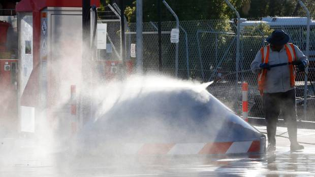 A contractor water blasts (for free) the Caltex truck stop fuel facility at Port Nelson.