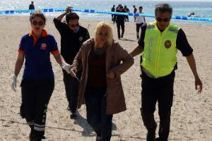 A woman, who survived after a plastic boat carrying Syrians to Greece sunk, is helped by a Turkish policeman and medics ...