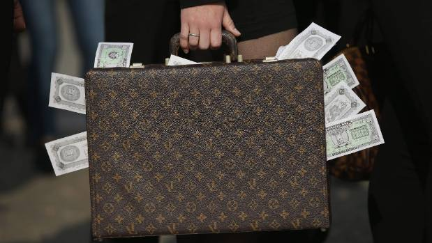An activist clutching a suitcase stuffed with fake money demands greater transparency in financial legislation following ...
