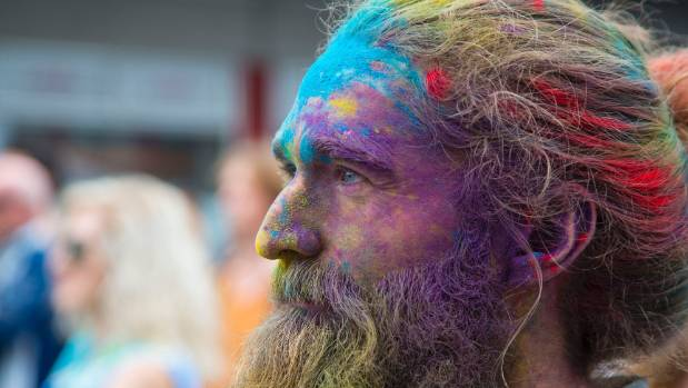 Andrew Strugnell, covered in dye from the Holi Wellington Colour Festival, enjoys a band.