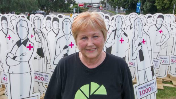 Healthcare assistant Bev Watt in front of 200 life-size cutouts, each the equivalent of 100 health workers, to represent ...