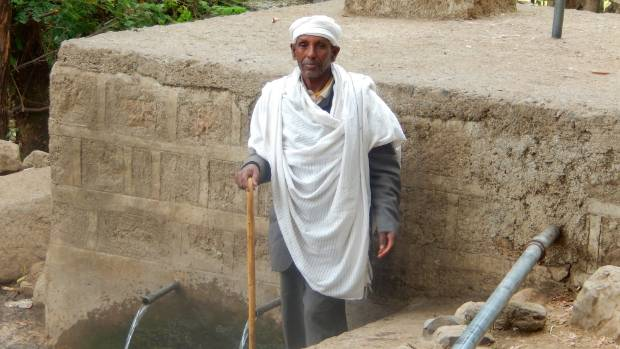 Amlaku Teshome's father, in front of the clean water tank, that now keeps cattle from walking through the village's ...