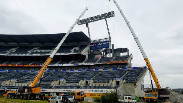 Cranes removing the lights at Lancaster Park, which will be demolished.