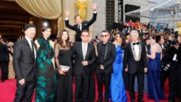 Actor Benedict Cumberbatch jumps behind U2 at the 86th Academy Awards in Hollywood, California.