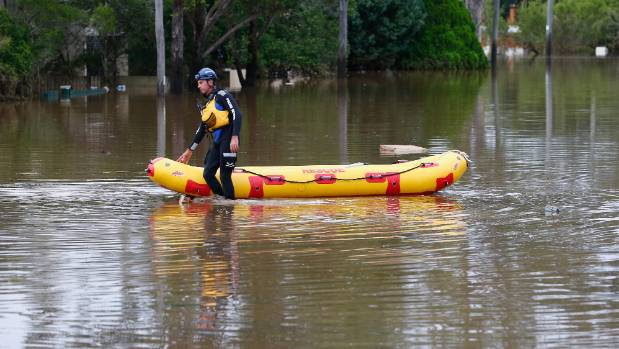 A State Emergency Service worker paddles down a flooded street in Lismore, NSW.