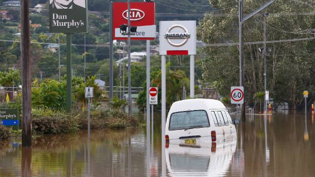 A van is partially submerged in a flooded Lismore street.