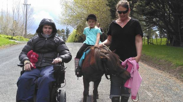 Ben Clifford walks daughter Alizay's pony Teddy with Ben's mother Kellie Aitchison.