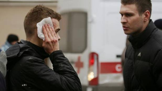 An injured person stands outside Sennaya Ploshchad metro station in St Petersburg, Russia, after an explosion.