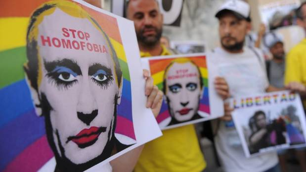 Protestors hold graphic images of Russian President Vladimir Putin wearing lipstick during a protest against Russian ...