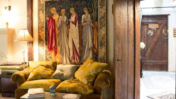 Another Burne-Jones reproduction tapestry warms up the main living room; the timber doors were probably made by James ...