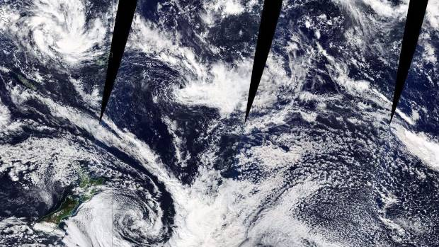A composite satellite image showing the ex-cyclone to the east of New Zealand. A tropical disturbance can be seen at top ...