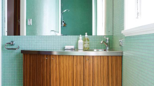 The original 1930s shower room has been retiled with teal green mosaics, following the curved wall, and fitted with a ...