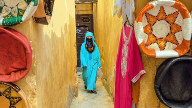 A woman in blue djellaba walkis through the medina in Fez.