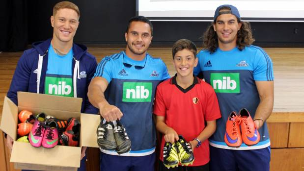 Blues players Declan O'Donnell, Sam Nock, and Kara Pryor pick up pre-loved rugby boots from Remuera intermediate student ...