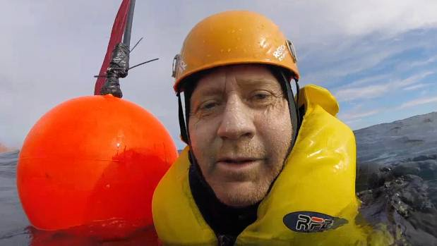 Russel Norman from Greenpeace swims in front of an oil exploration ship.