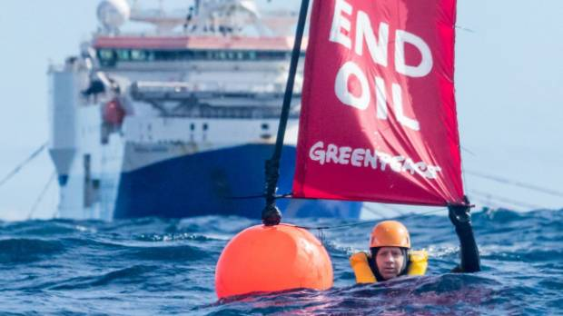 Three Greenpeace activists, including executive director Russel Norman, swam in front of the Amazon Warrior off the ...