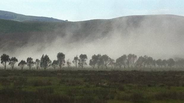 Lime is sprayed over a farm alongside Lake Ellesmere on a strong northerly day, blowing the lime into the lake.