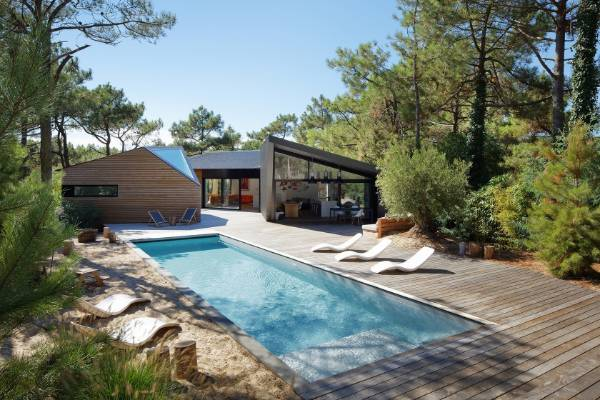 The Cap Ferret holiday house recalls a cabin, with three linked pavilions that are open to a deck and pool.