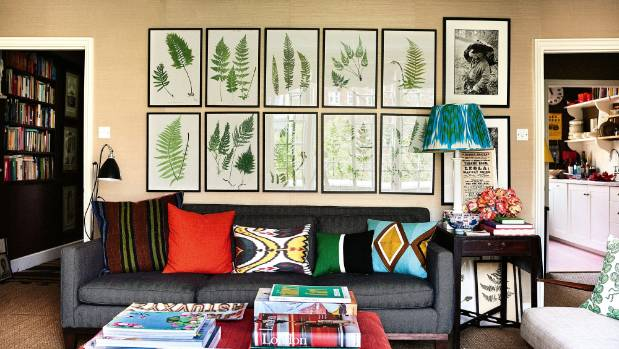 Framed ferns printed from copper plates fill the wall behind the grey sitting room sofa from Crate & Barrel in New York, ...