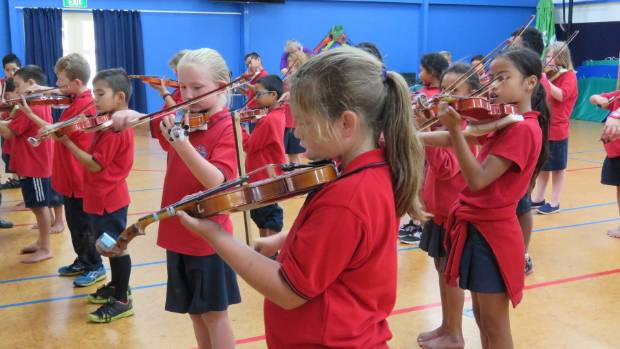 Children learning to play the violin.