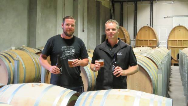 Sebastian Hanse and Roy Kamphuis with their Trinity Hill IPA in the winery's barrel room.