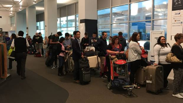 Passengers queuing at Auckland Airport's domestic terminal as ex-tropical Cyclone Cook disrupts flights out of the city.