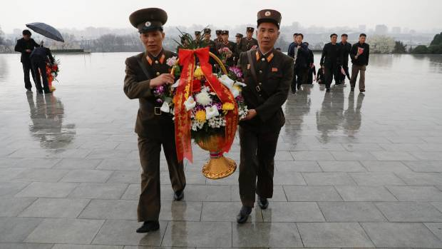 Soldiers carry flowers as they arrive to pay respects at the statues of North Korea founder Kim Il Sung and late leader ...
